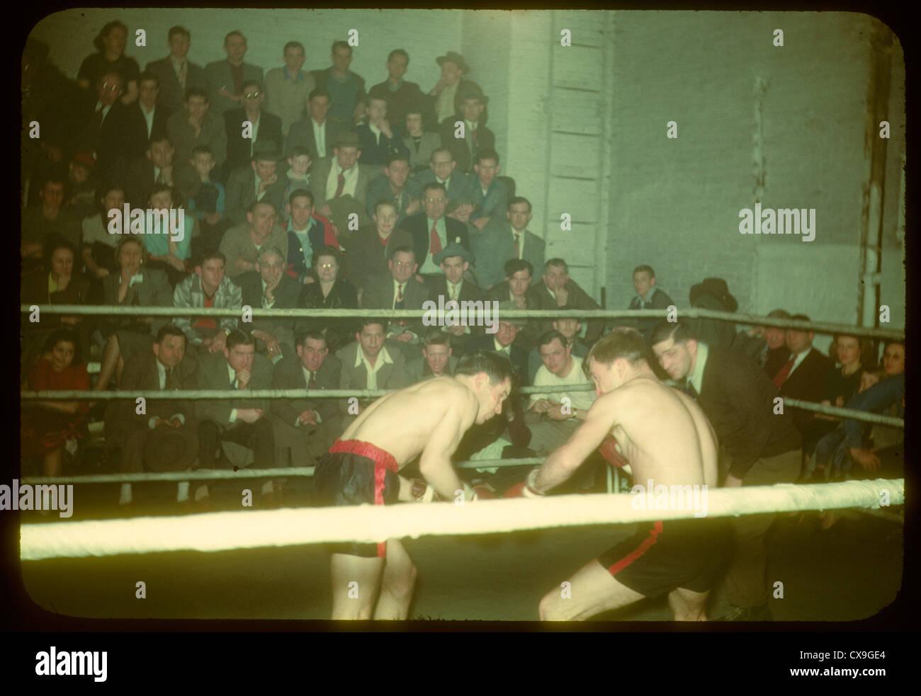 Incontro di boxe sport 1950 boxer sbarco punzone di soffiaggio color kodachrome fighters fighting lotta ring pubblico Immagini Stock