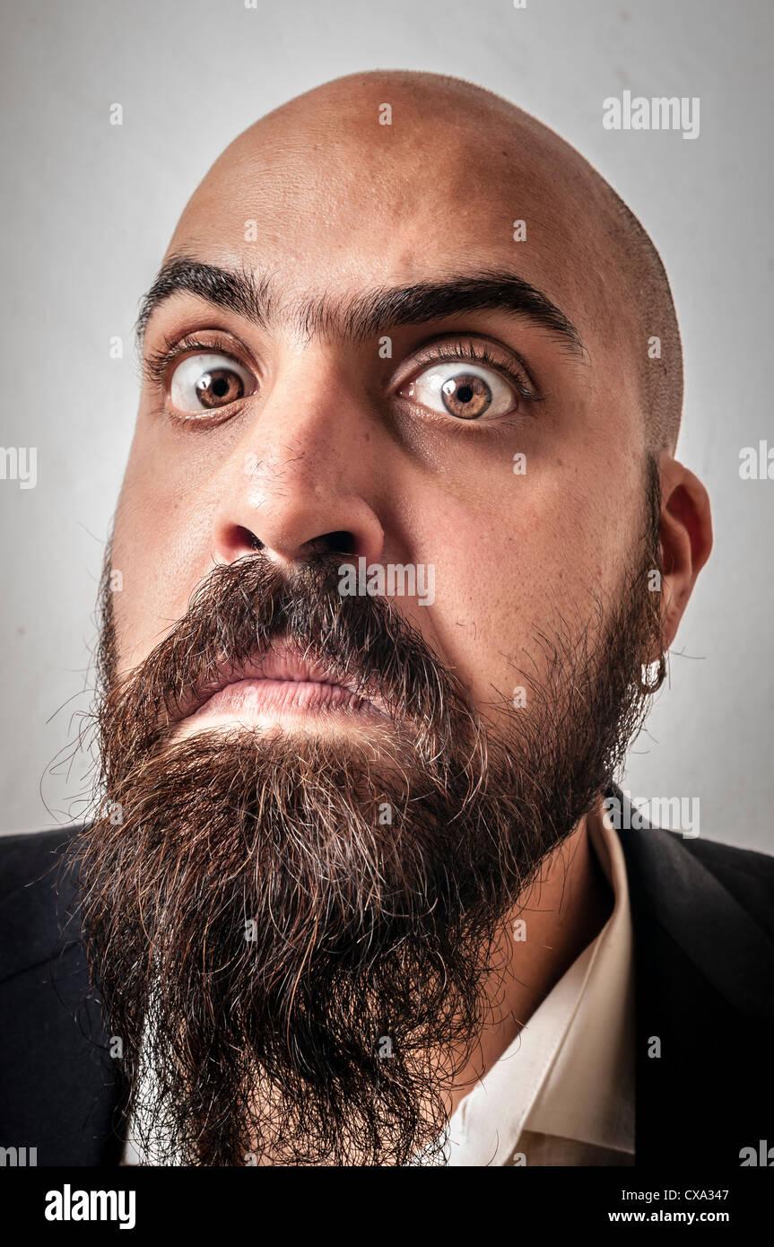 Uomo con una tuta e barba e le espressioni di strano su sfondo bianco Immagini Stock
