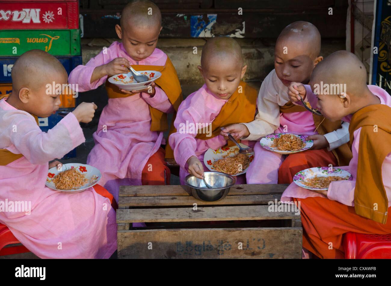 Giovane debuttante monache aventi la loro prima colazione nelle strade di Yangon, Myanmar (Birmania), Asia Immagini Stock