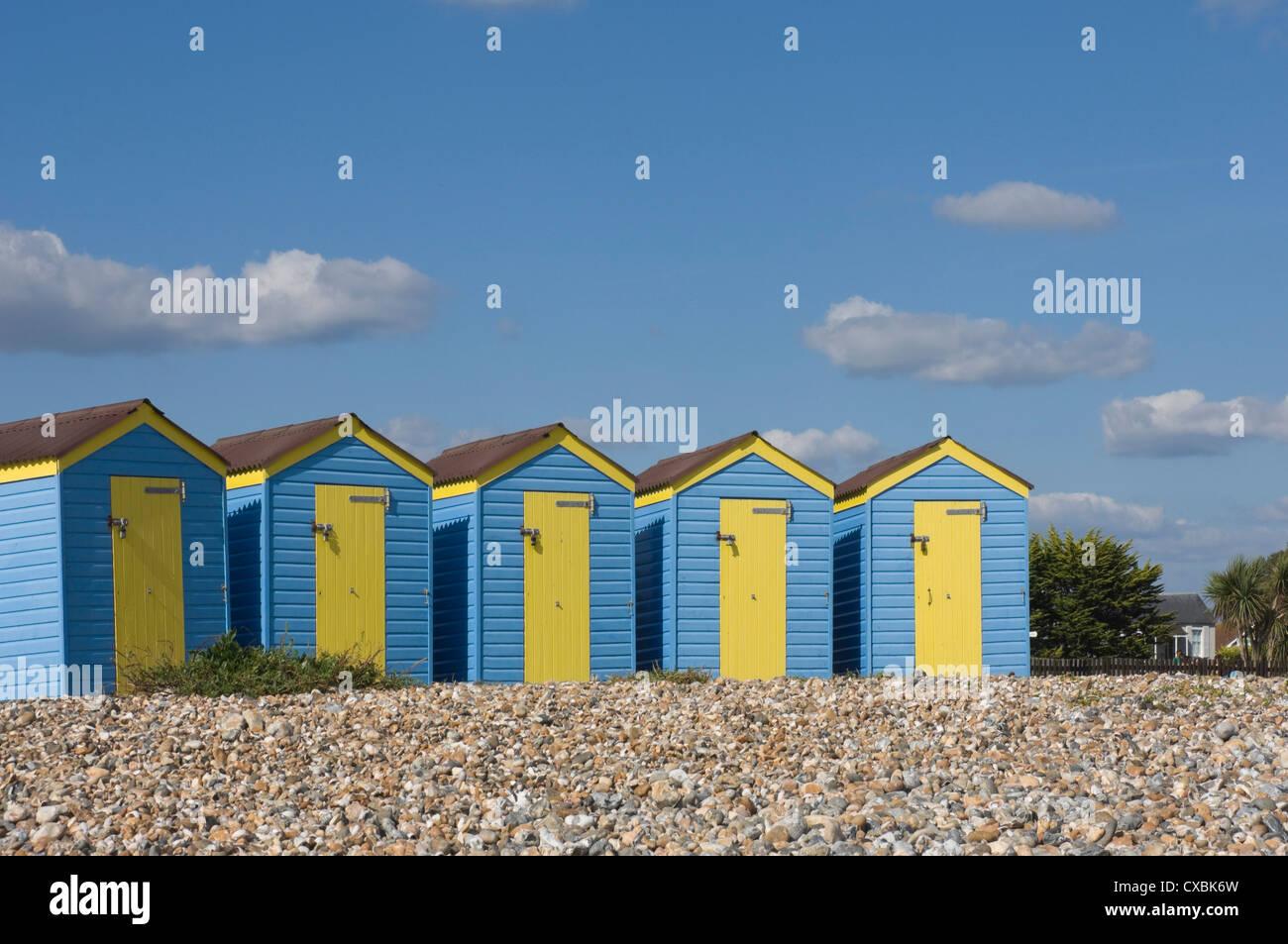 Cinque blu spiaggia capanne con sportelli gialli, Littlehampton West Sussex, in Inghilterra, Regno Unito, Europa Immagini Stock