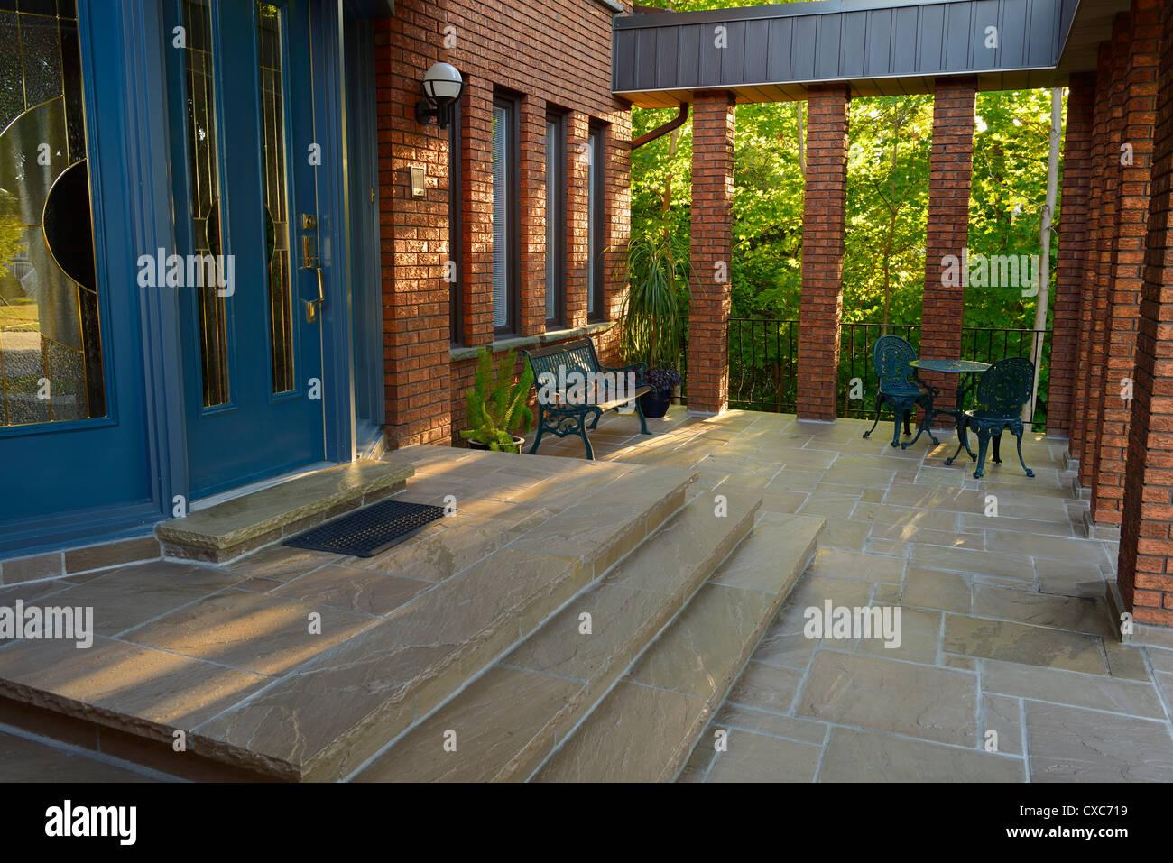 Anteriore porta blu e pietra portico di casa in mattoni rossi con pilastri al tramonto toronto Immagini Stock