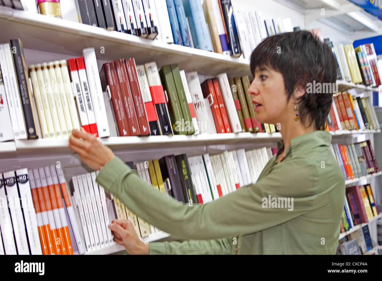 Donna che guarda i libri di una libreria Immagini Stock