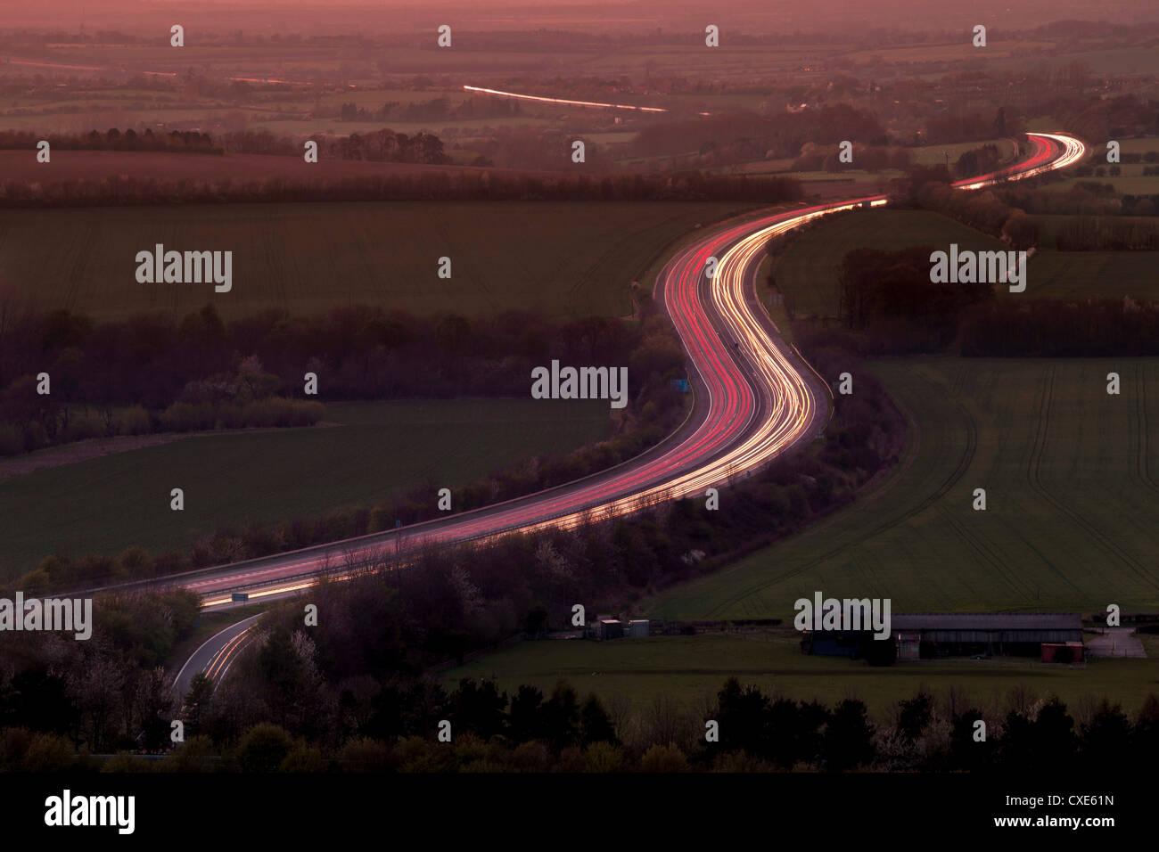 Teleobiettivo con vista aerea di sentieri di luce al tramonto su autostrada M40 in Chilterns, Oxfordshire, England, Immagini Stock