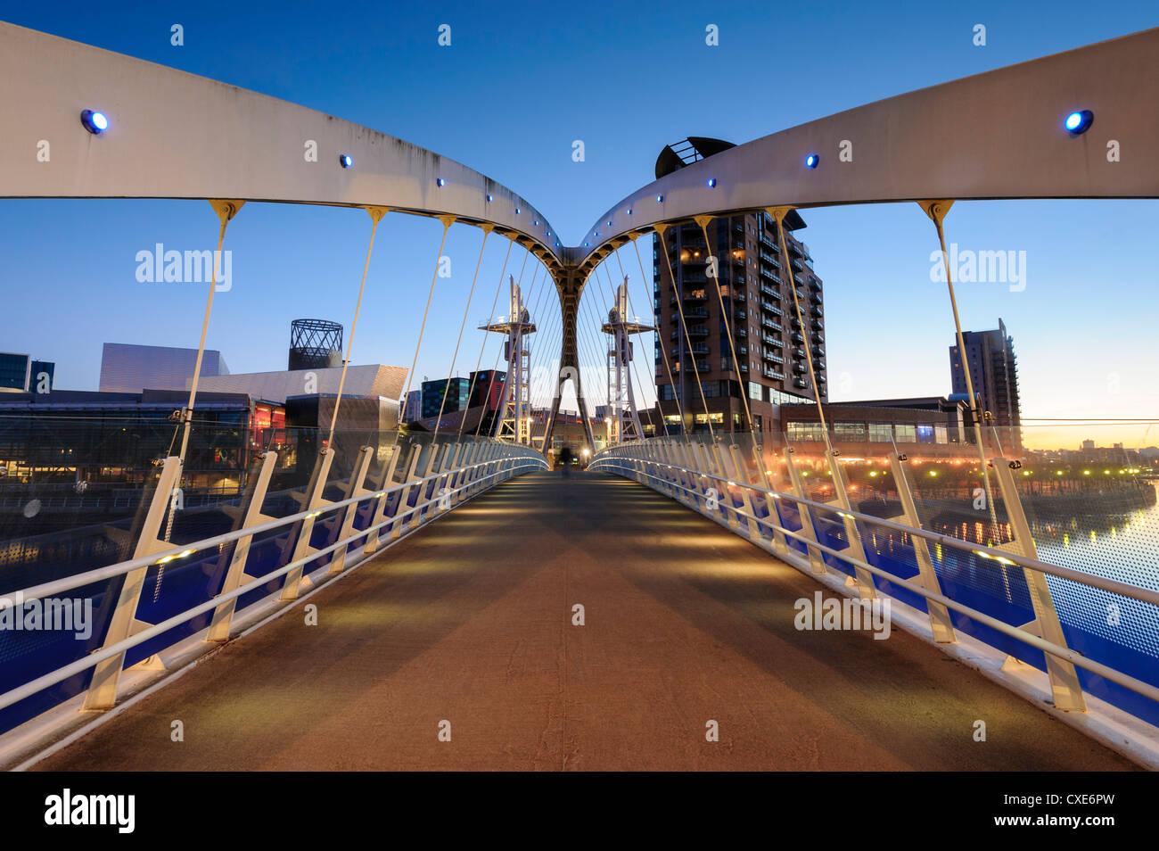 Alba vista attraverso il Millennium Bridge, Salford Quays, Manchester, Greater Manchester, Inghilterra, Regno Unito, Immagini Stock