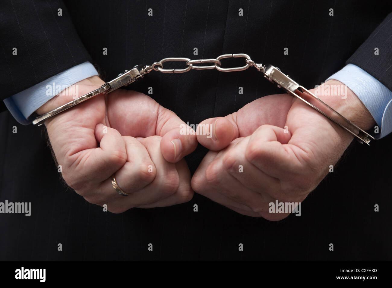Uomo in un business suit con le mani in mano polsini a significare un White Collar Crime Immagini Stock