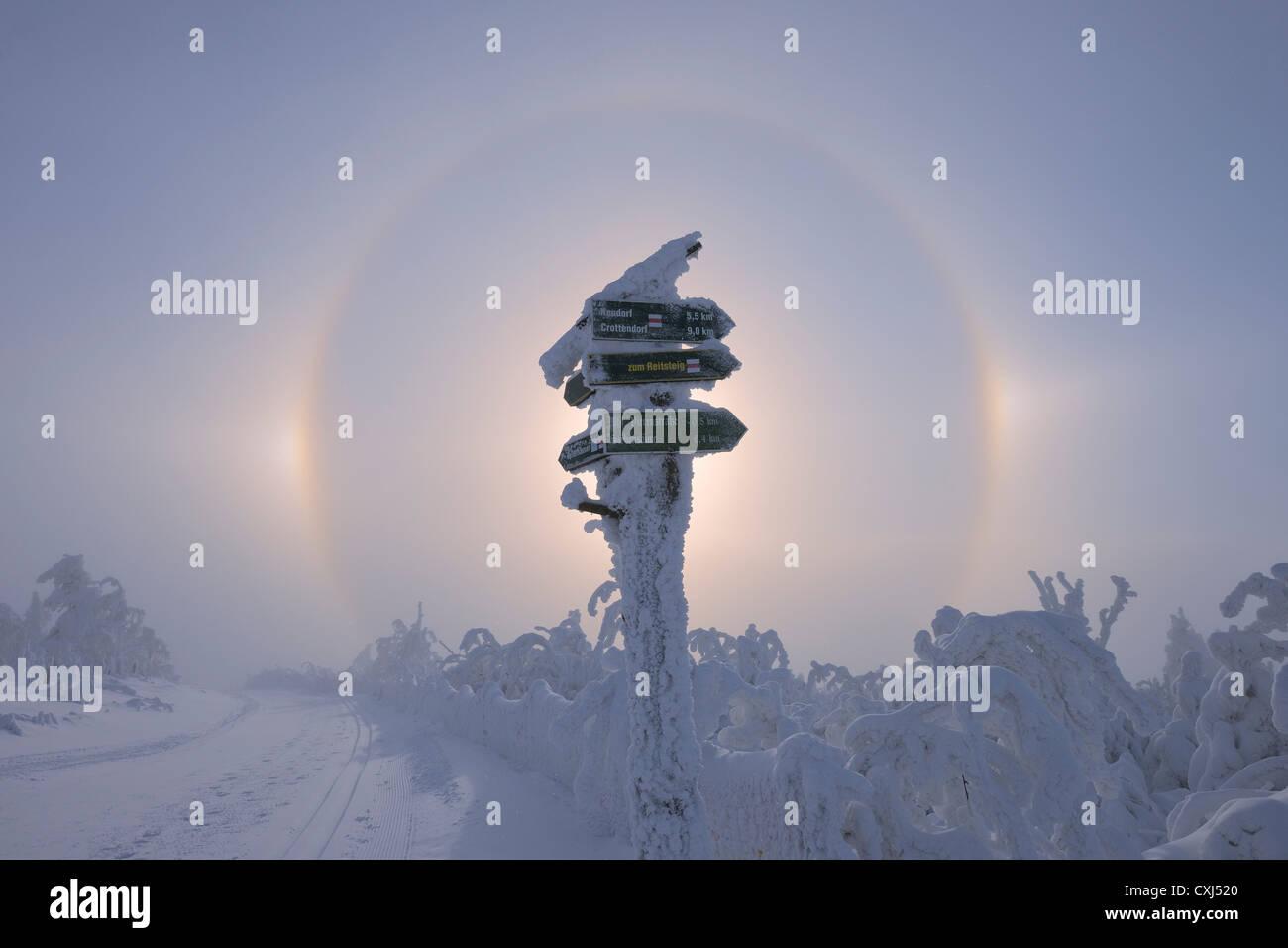 Vista di sundog con segno direzionale nel paesaggio innevato Foto Stock