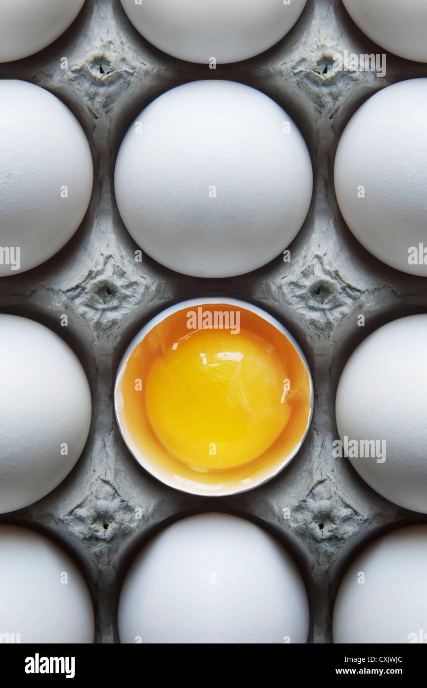 Uova in scatola di cartone con un guscio rotto Foto Stock