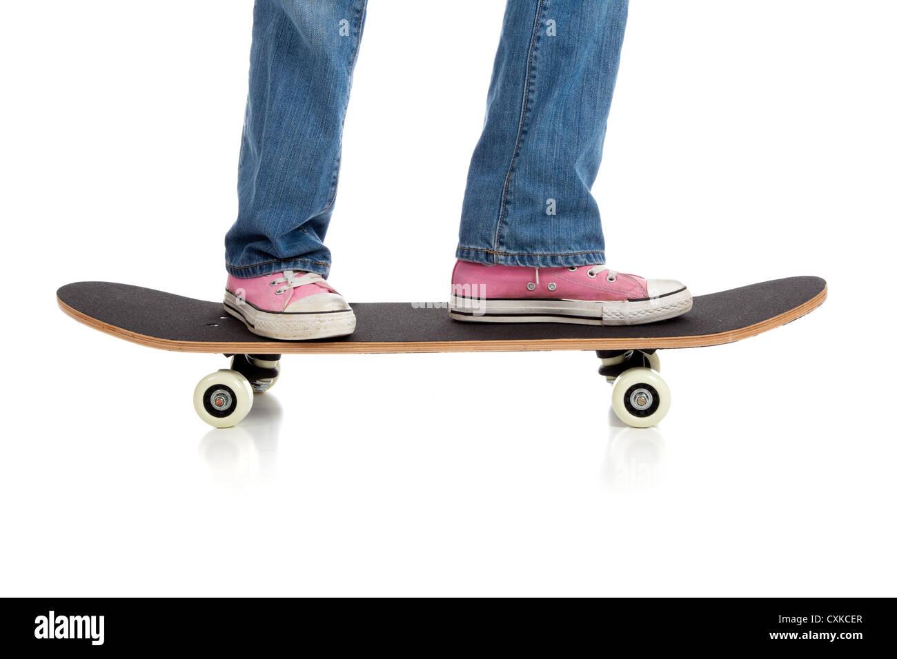 Sneakers rosa su uno skateboard Immagini Stock