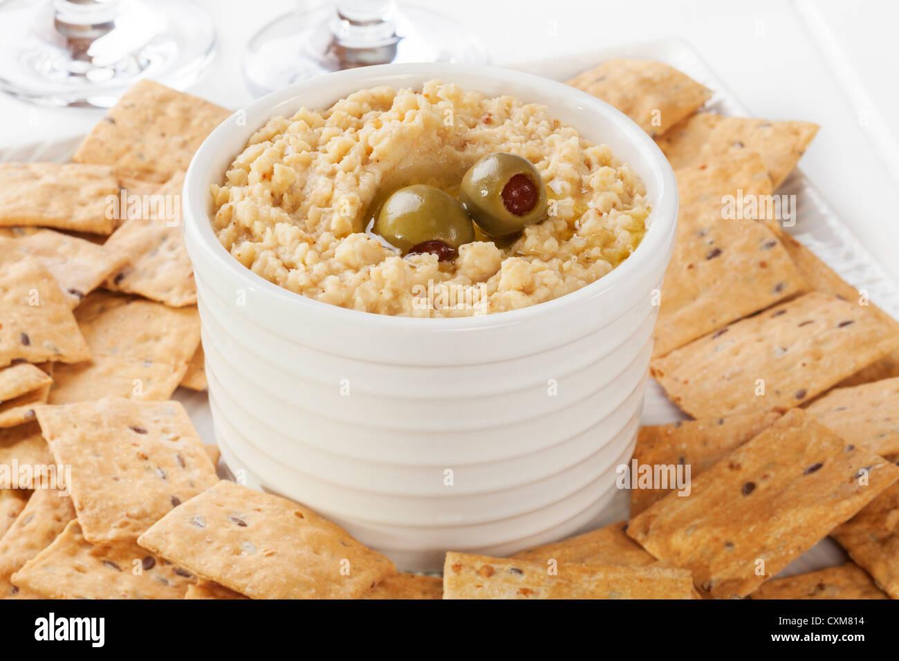 Hummus servita con cracker. A basso contenuto calorico con la versione meno olio. Immagini Stock