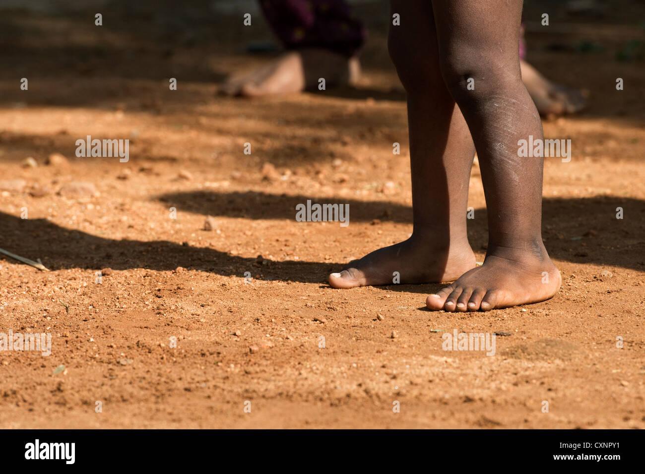 Bambini indiani gambe nude e piedi getta un' ombra sulla terra in un territorio rurale villaggio indiano. Andhra Immagini Stock