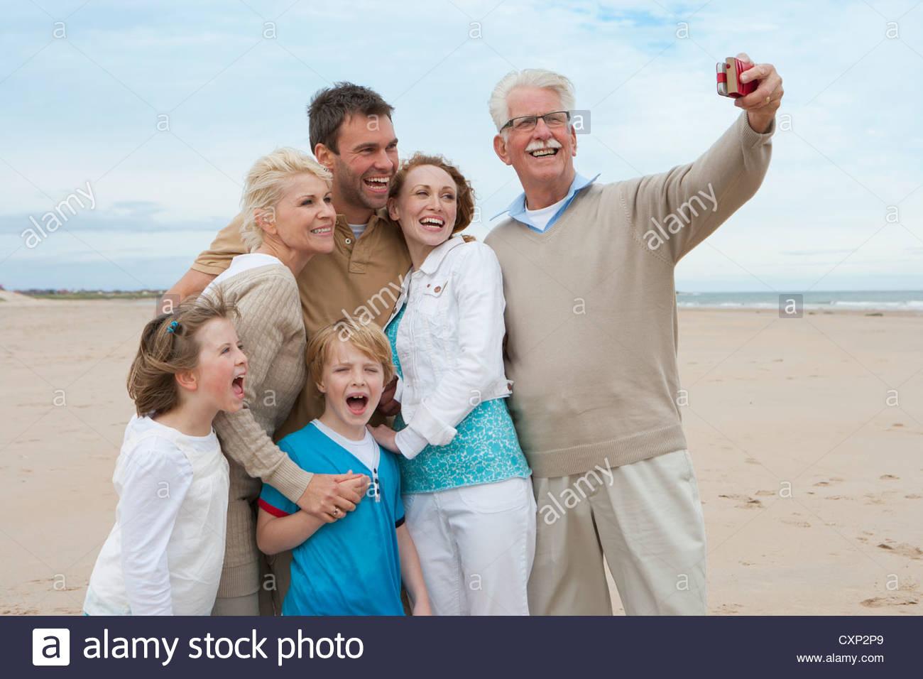 Prendendo foto di Multi generazione Famiglia in vacanza in spiaggia Immagini Stock