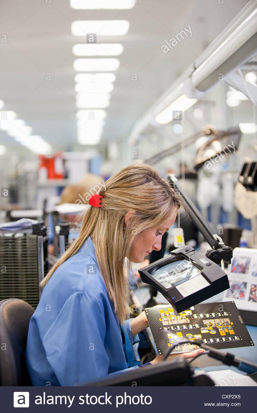Il tecnico di esaminare la scheda a circuito stampato in hi-tech electronics impianto di fabbricazione Immagini Stock