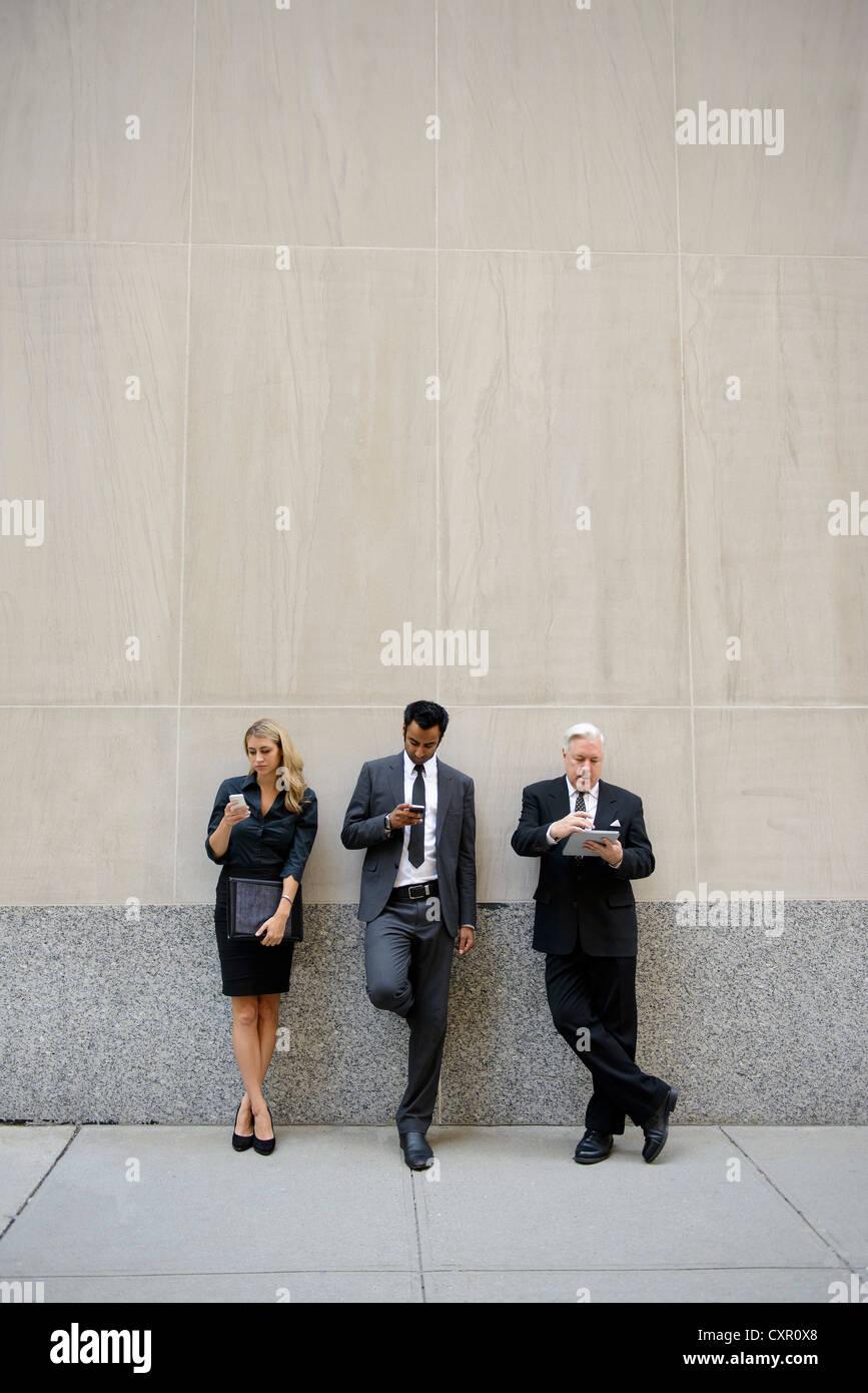 Tre imprenditori appoggiato su di una parete, guardando a telefoni digitali e compresse Immagini Stock