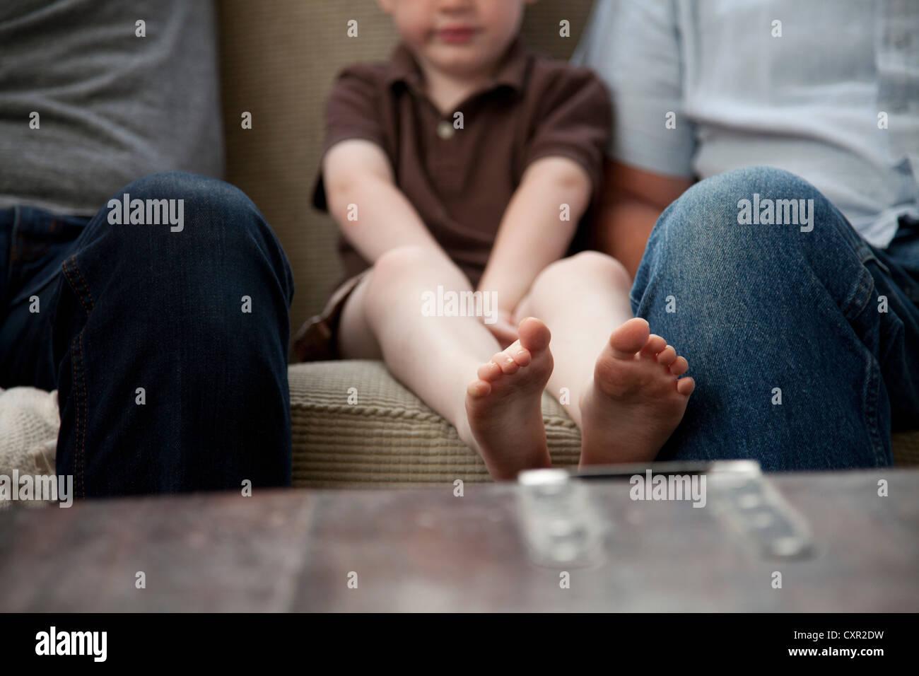 Ragazzo seduto sul divano con adulti Immagini Stock
