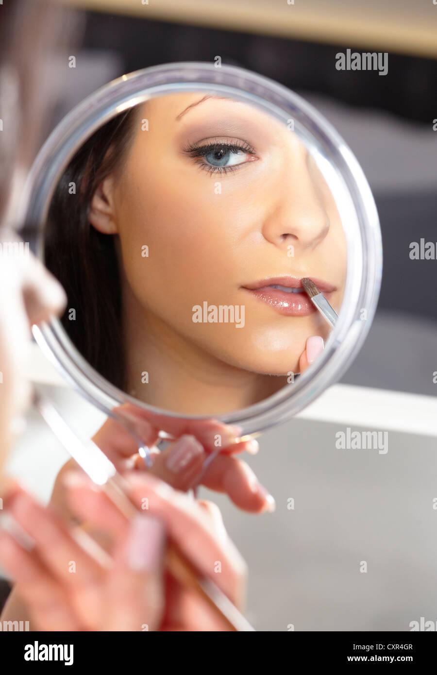 Giovane donna tenendo una mano specchio e una spazzola di rossetto Immagini Stock
