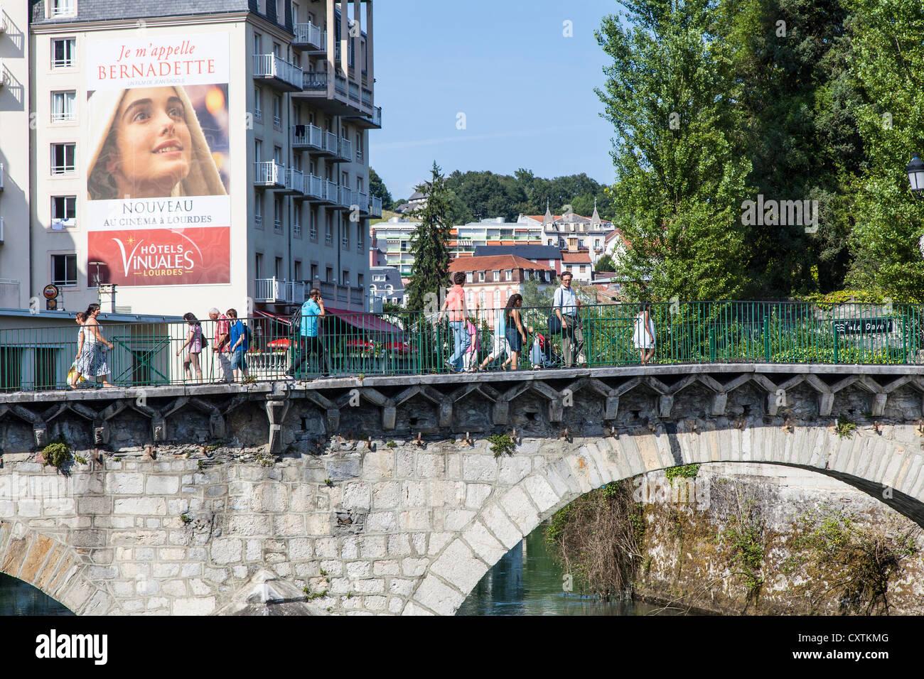 Ponte sul fiume Gave de Pau a Lourdes con Bernadette poster, Hautes Pirenei, Francia Immagini Stock
