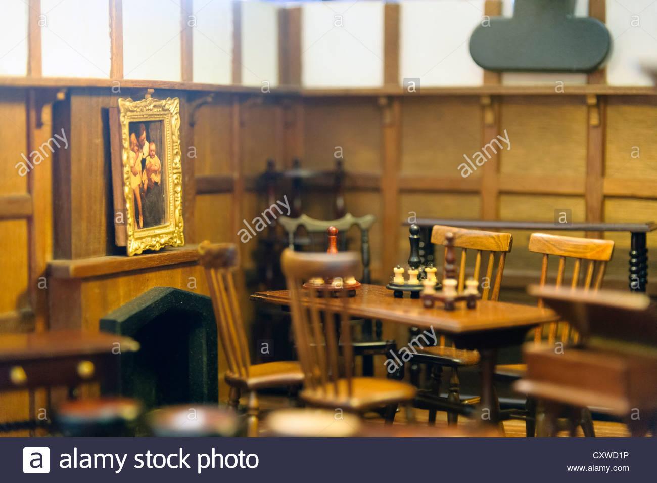 Dolls house mobili in una camera in miniatura con tavolo, sedie e pittura. La base di una clip sulla luce è Immagini Stock