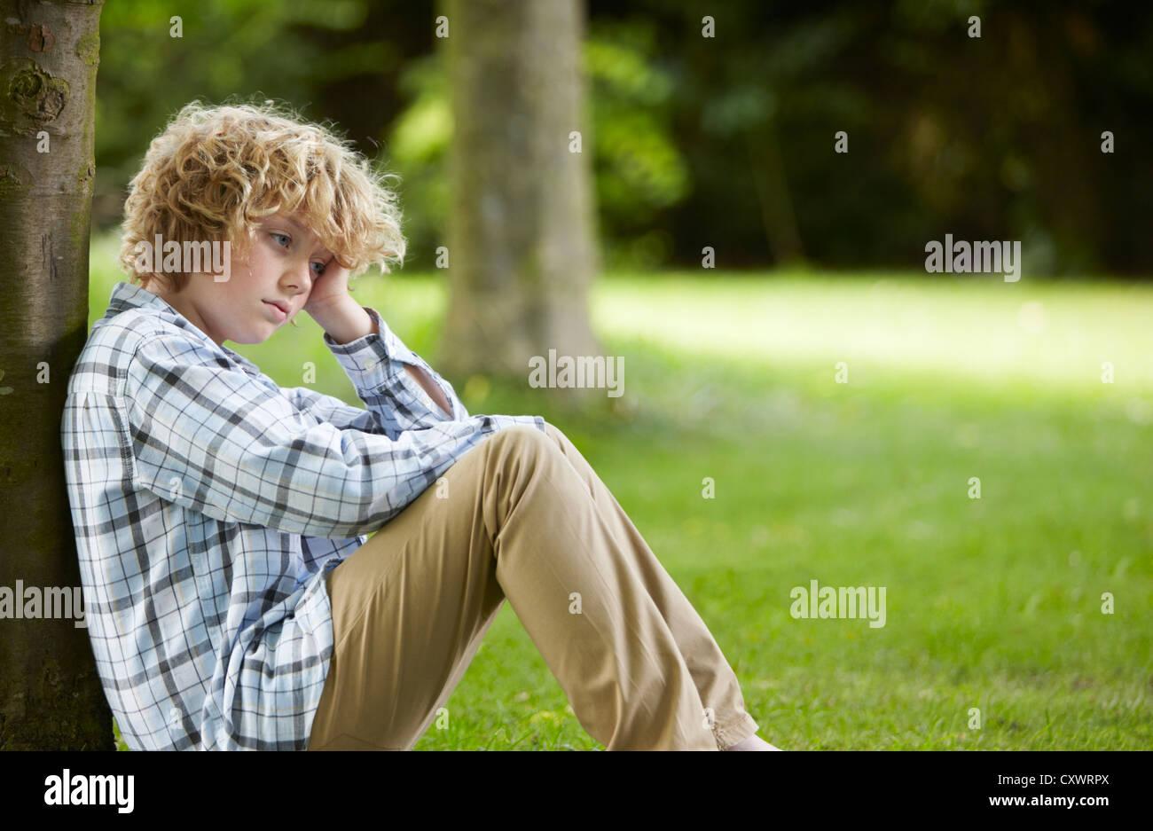 Triste cerca ragazzo appoggiata ad albero Immagini Stock