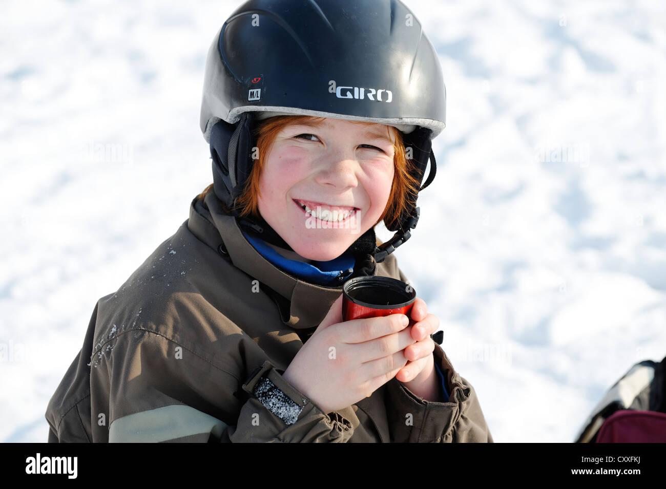 Ragazzo di bere una tazza di tè nel corso di sport invernale sulla neve Immagini Stock