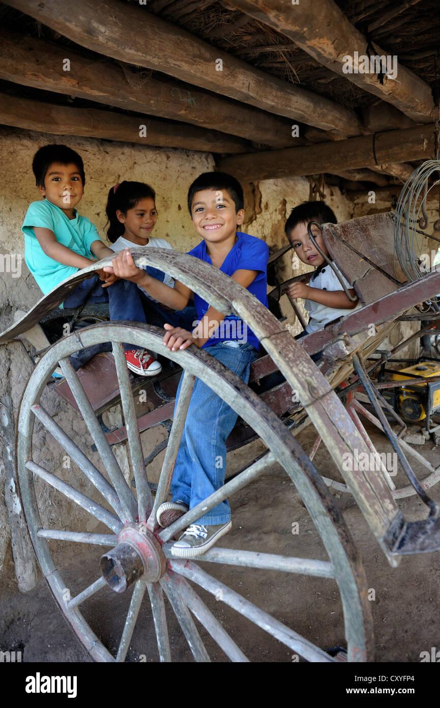 Bambini che giocano su un carrello di una fattoria tradizionale Gran Chaco, Santiago del Estero Provincia, Argentina, Immagini Stock