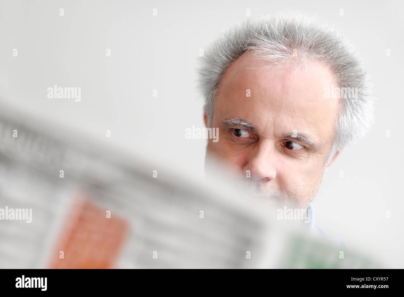 Un uomo che legge un giornale di essere stupito, Renania settentrionale-Vestfalia Immagini Stock
