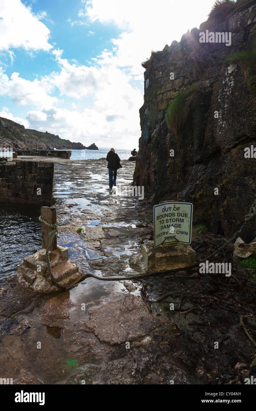 Signora oltrepassando cartello fuori dai limiti a causa di danni provocati dalla tempesta a Lamorna Cove, Cornwall Immagini Stock