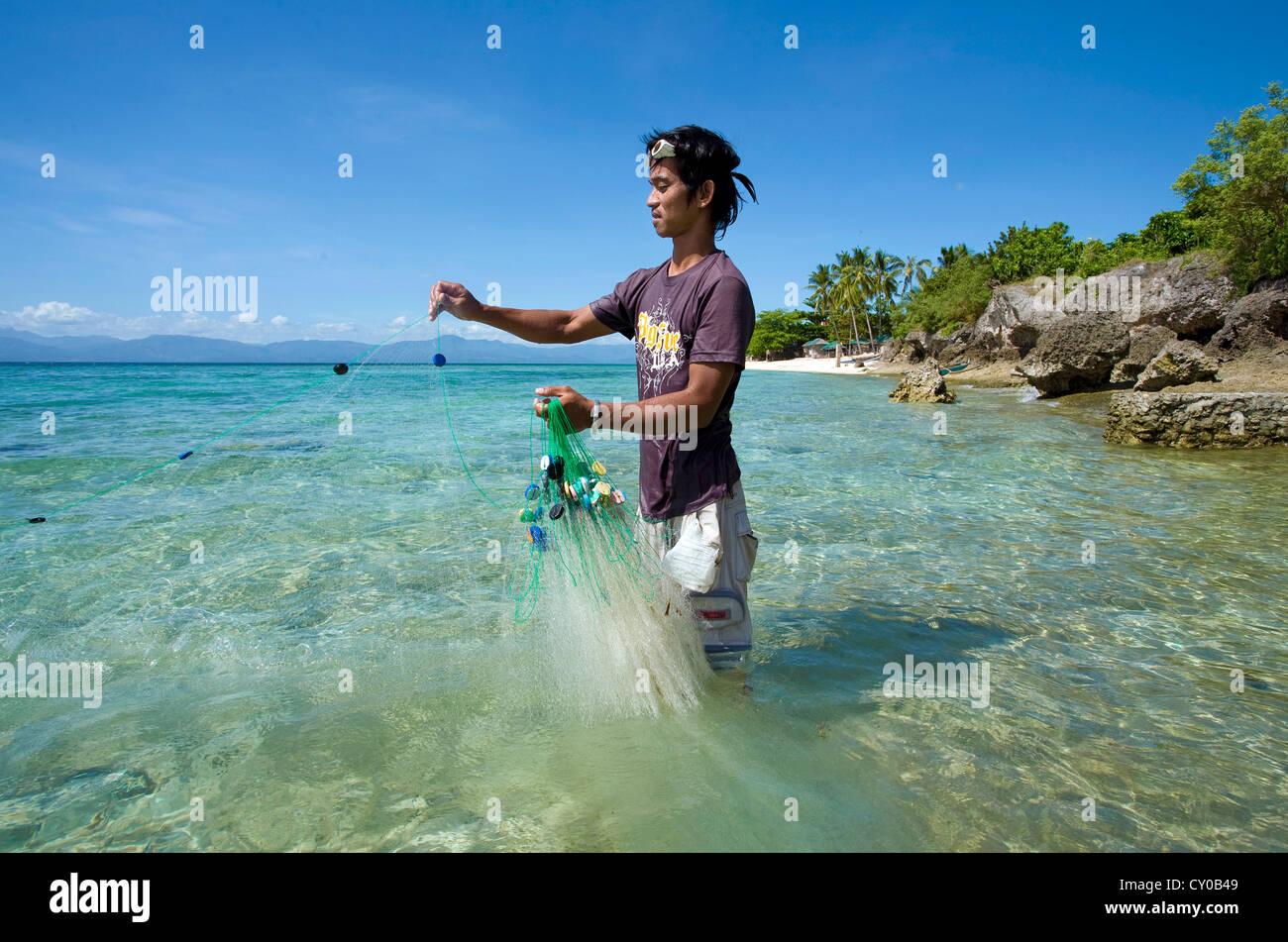 Philippine pescatore piccolo di cattura di pesci da esca con un net, spiaggia bianca, Moalboal, Cebu, Filippine, Foto Stock