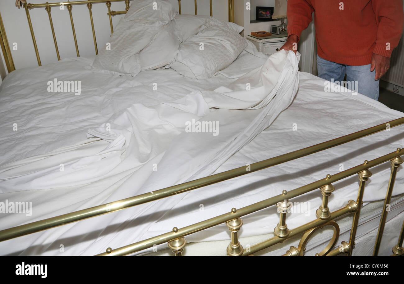 L'uomo cambiare le lenzuola del letto Immagini Stock