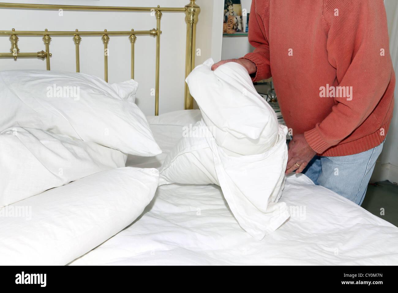 L'uomo cambiare le lenzuola rimozione federa Immagini Stock