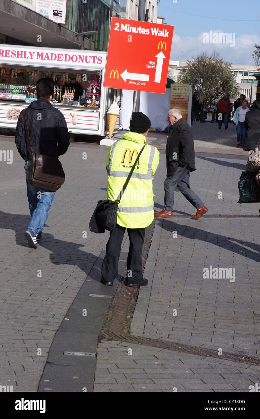 Uomo con mcdonalds segno a Birmingham Regno Unito Foto Stock