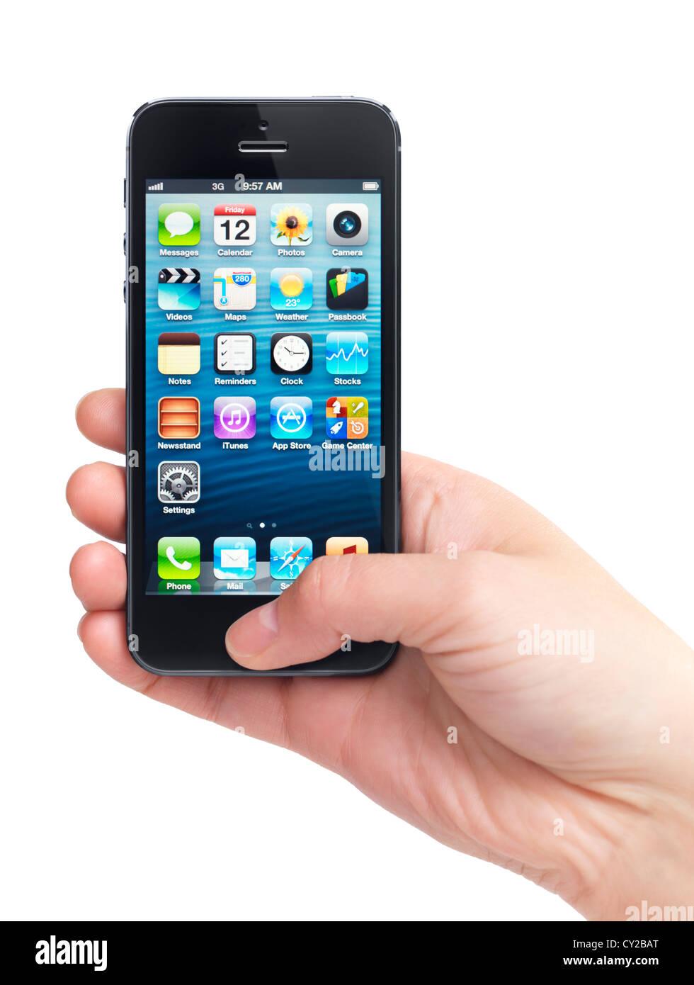 Close up di una mano tiene iPhone 5 con blue desktop sul suo display isolati su sfondo bianco Immagini Stock