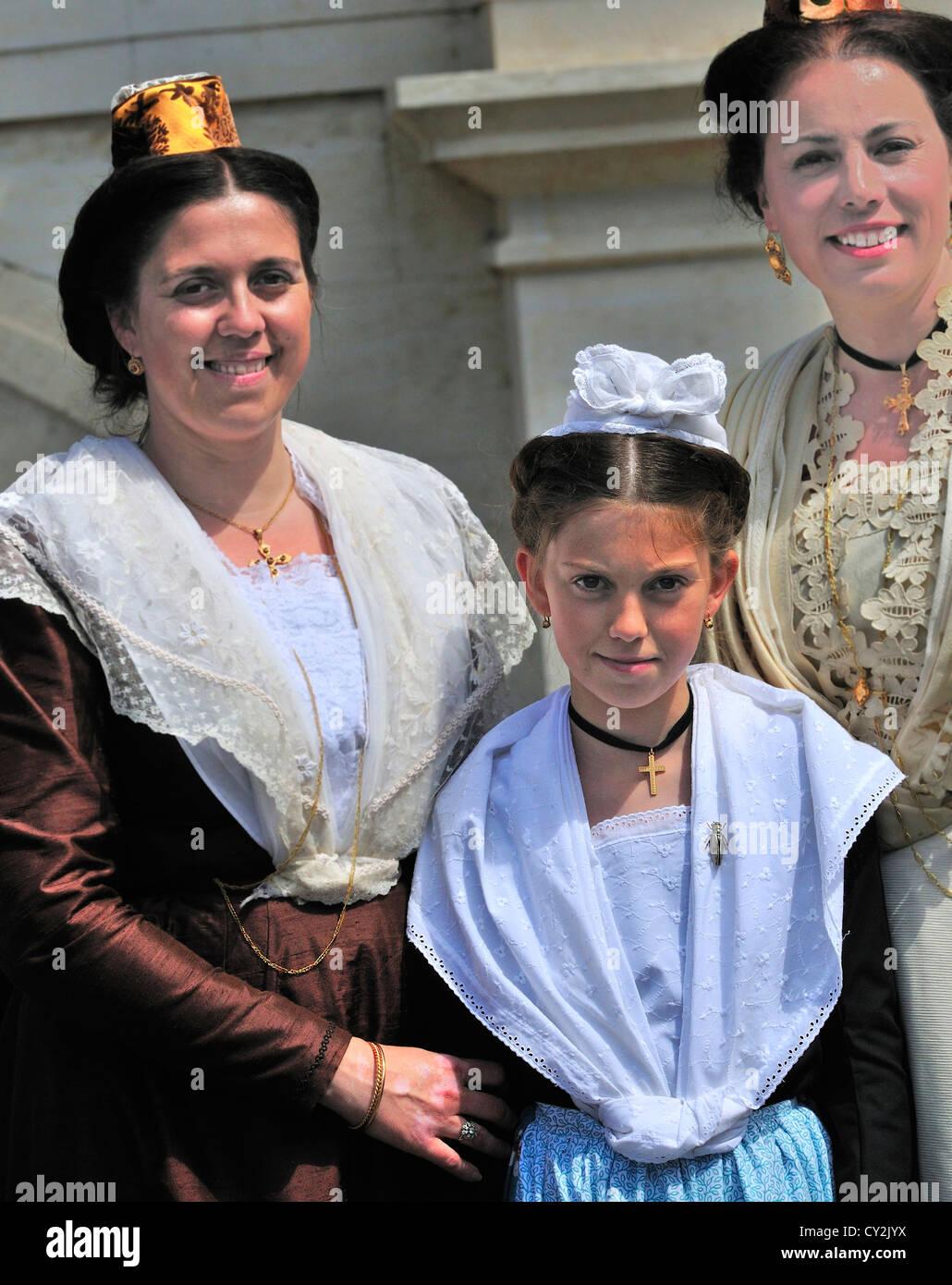 Onorevoli ragazza in costume tradizionale come è il derigger tutori per mogli e Beauxs durante la Fete des Immagini Stock
