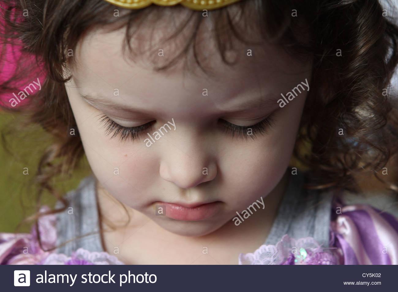 Una chiusura del volto di un bambino di 4 anni ragazza con abbattuto gli occhi. Immagini Stock