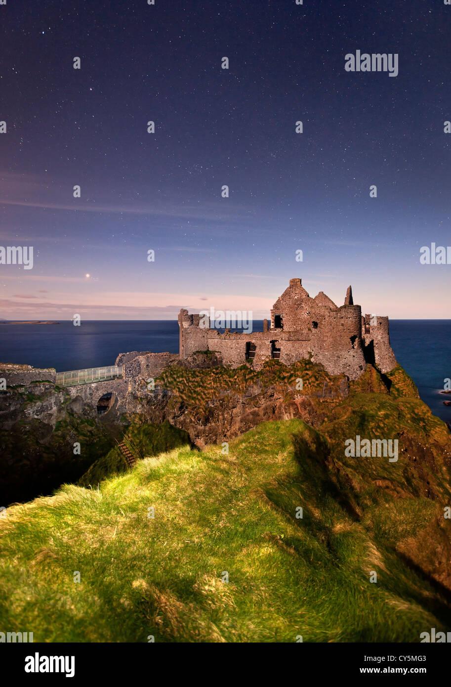 Dunluce Castle catturati durante la notte alla luce della luna. Immagini Stock