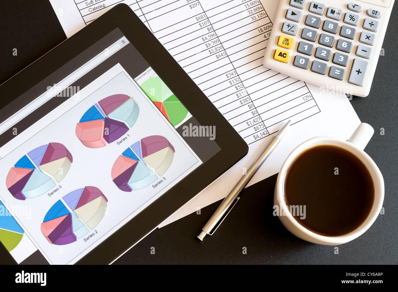 Ambiente di lavoro moderno con tavoletta digitale che mostra grafici e schema sullo schermo, caffè, penna e Immagini Stock
