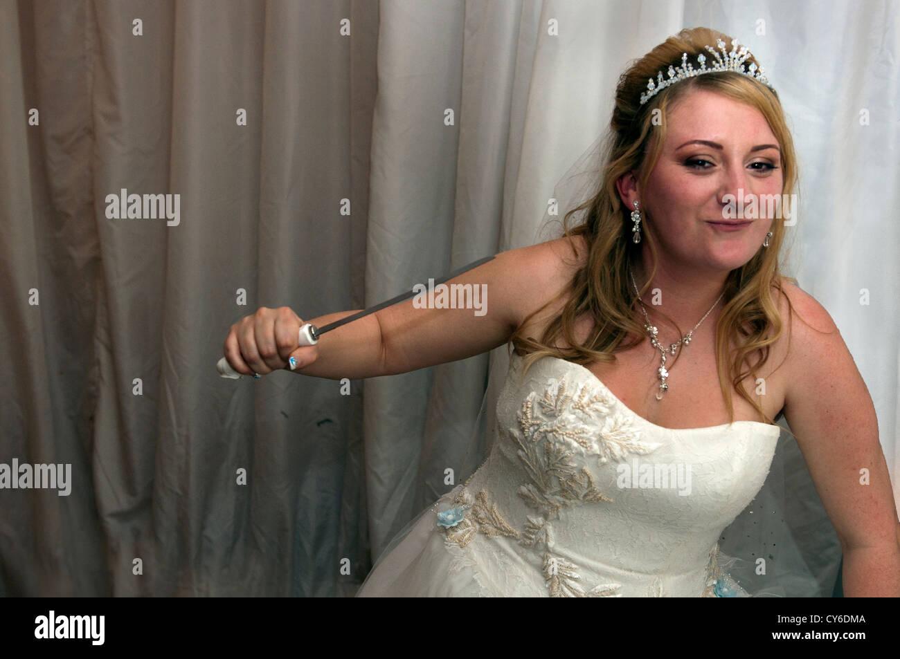 Modello rilasciato sposa tenendo un coltello (Bridezilla) al matrimonio Immagini Stock