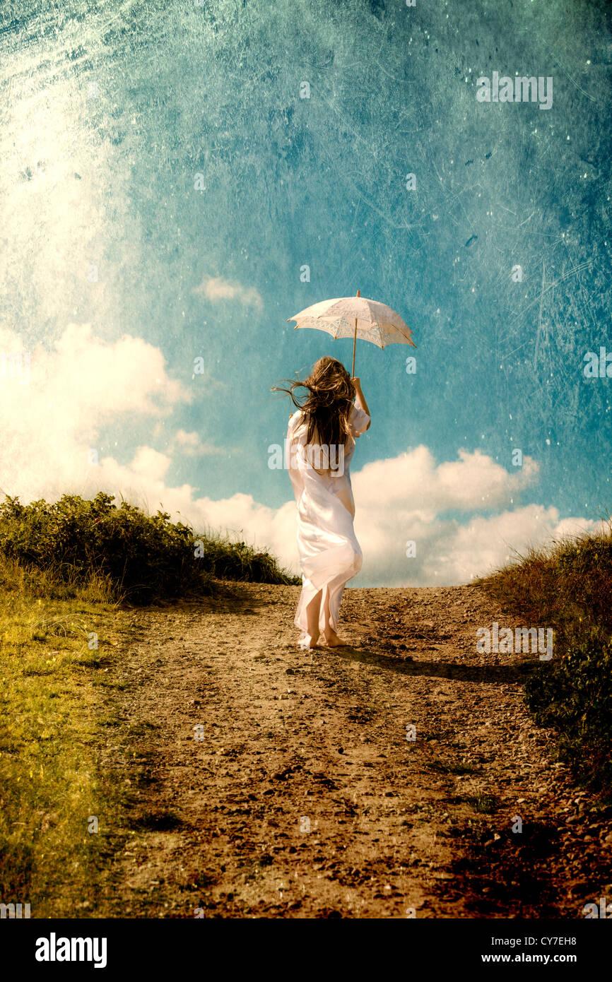 Una ragazza in un abito bianco è a piedi nelle dune con un ombrellone Foto Stock