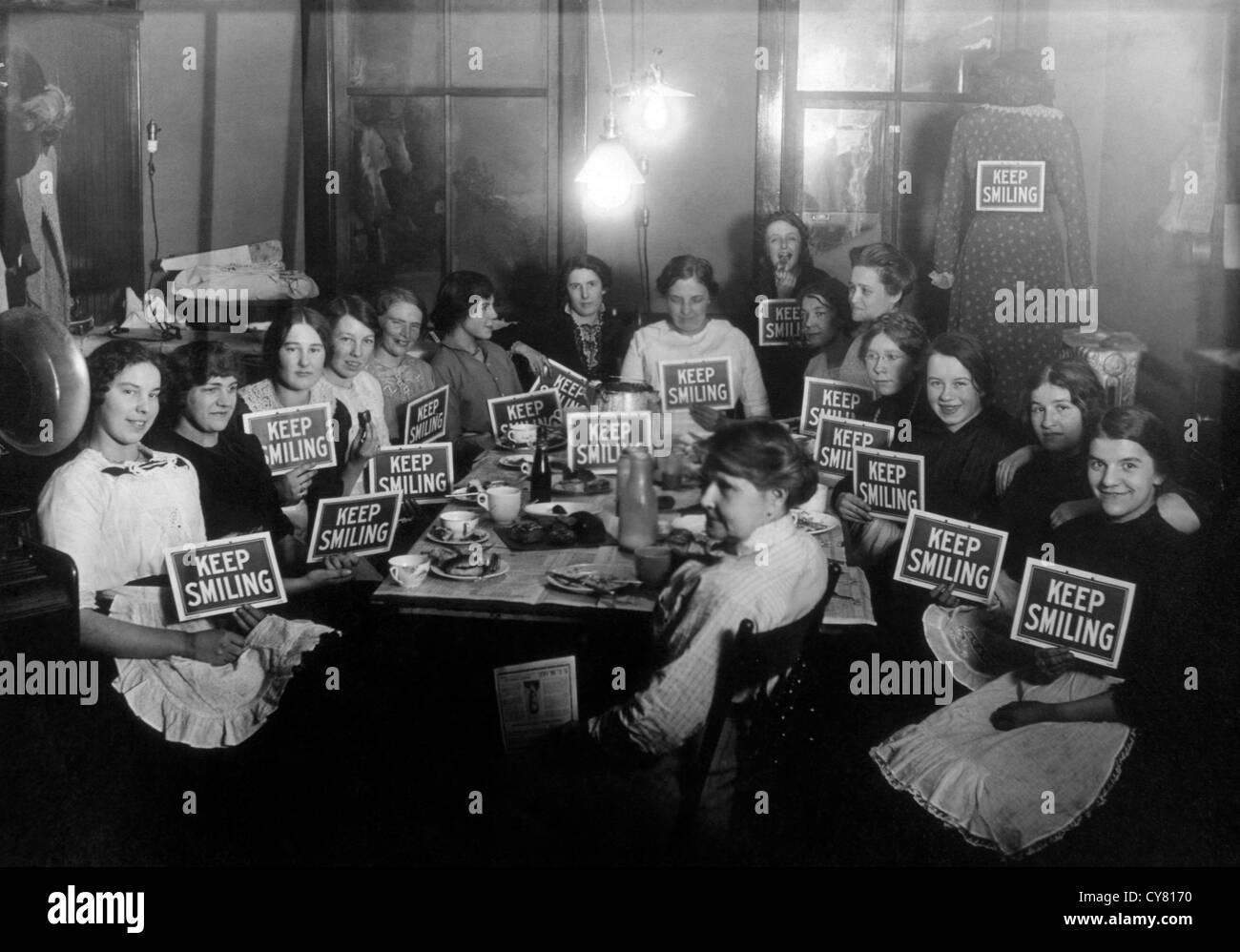 Seamstresses sulla pausa pranzo, tenendo continuare a sorridere segni, circa 1914 Foto Stock