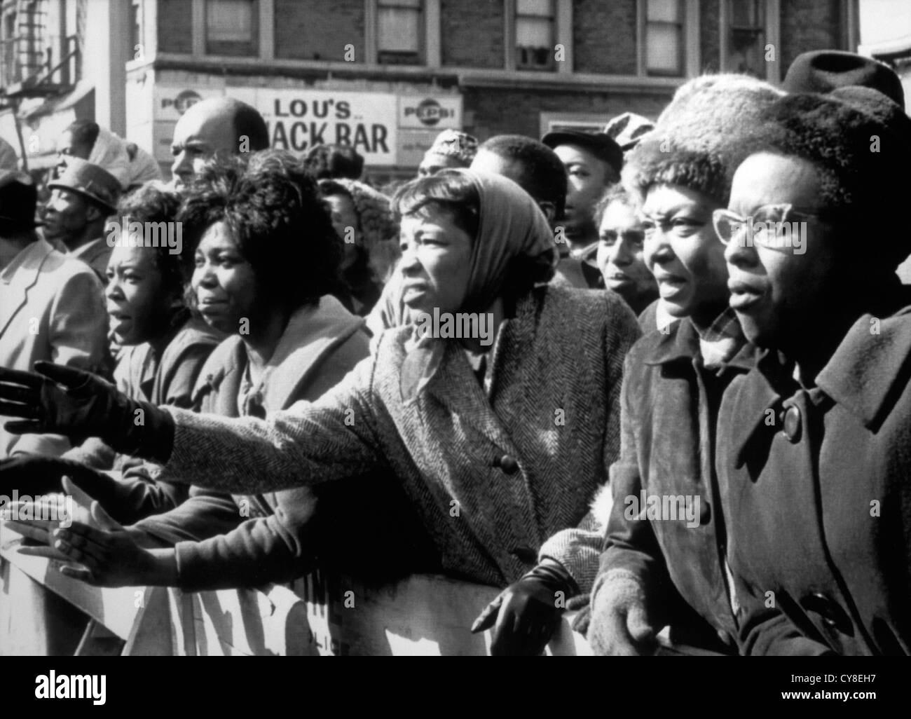 Sconvolto afro-americano di donne sventolare addio ucciso leader, Malcolm X, al tempio di fede, New York City, Stati Foto Stock