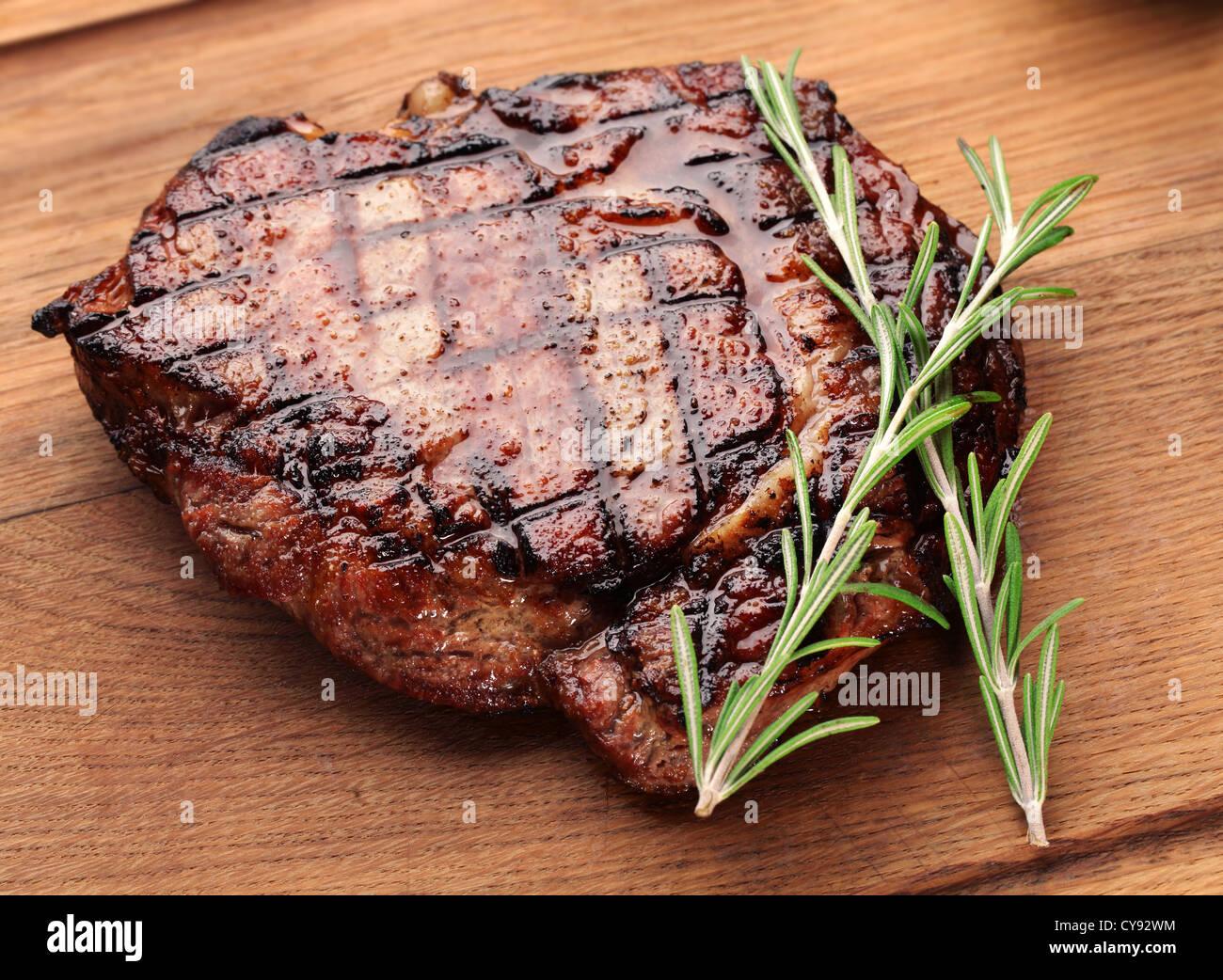 Bistecca su un tavolo di legno. Immagini Stock