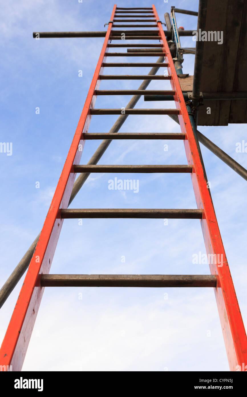 Red scaletta che conduce fino a una tavola per ponteggio dal piolo in basso contro il cielo blu per illustrare l' Immagini Stock