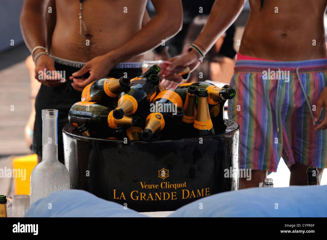 2 ragazzi in piedi accanto a decine di svuotare le bottiglie di champagne impilati in un secchiello per il ghiaccio,che Immagini Stock