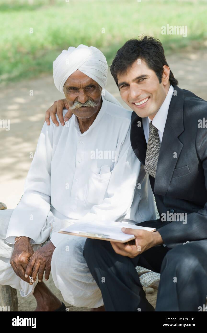 Advisor finanziario seduta con un imprenditore e sorridente Immagini Stock