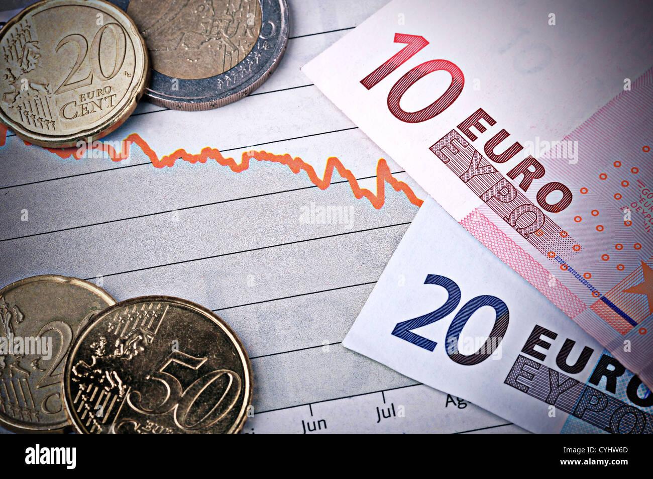 Un paio di banconote e monete sulla parte superiore di un grafico. Desature e con un look grintoso. Immagini Stock