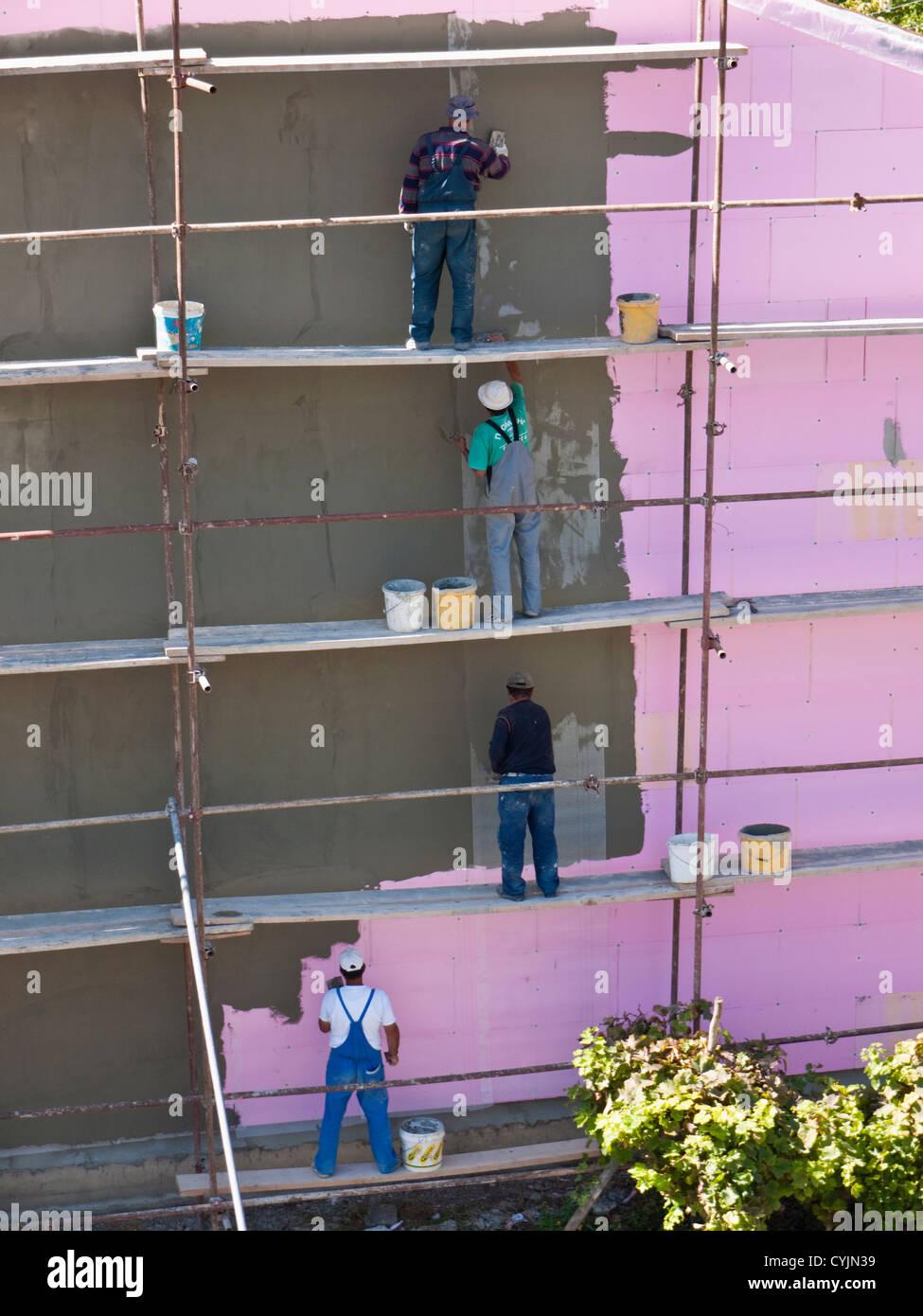 Lavoratori applicando il rendering di un edificio isolato a Ohrid Macedonia, dove gli standard di salute e sicurezza Immagini Stock