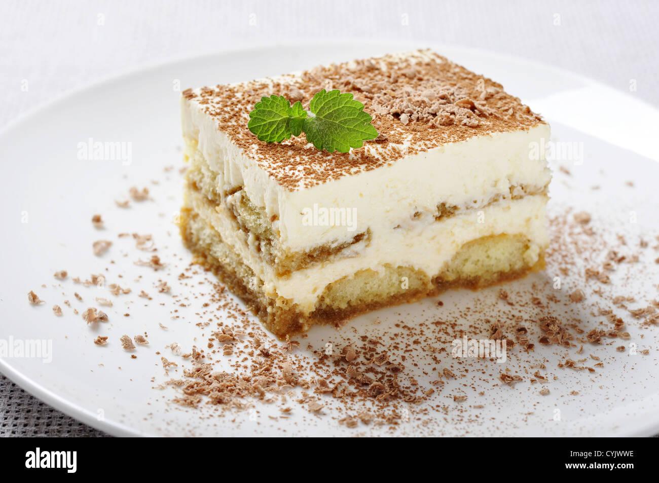 Il tiramisù - Classico dolce con il caffè sulla piastra bianca. Guarnite con foglie di menta. Immagini Stock