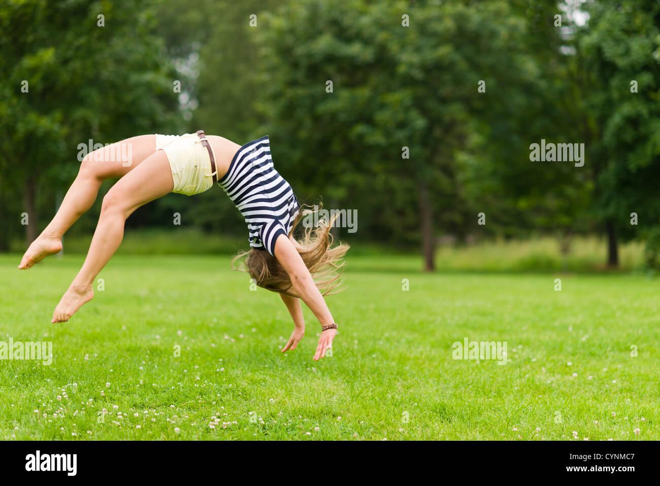 Giovane ragazza sportiva salta indietro al parco, immagine con profondità di campo ridotta Foto Stock