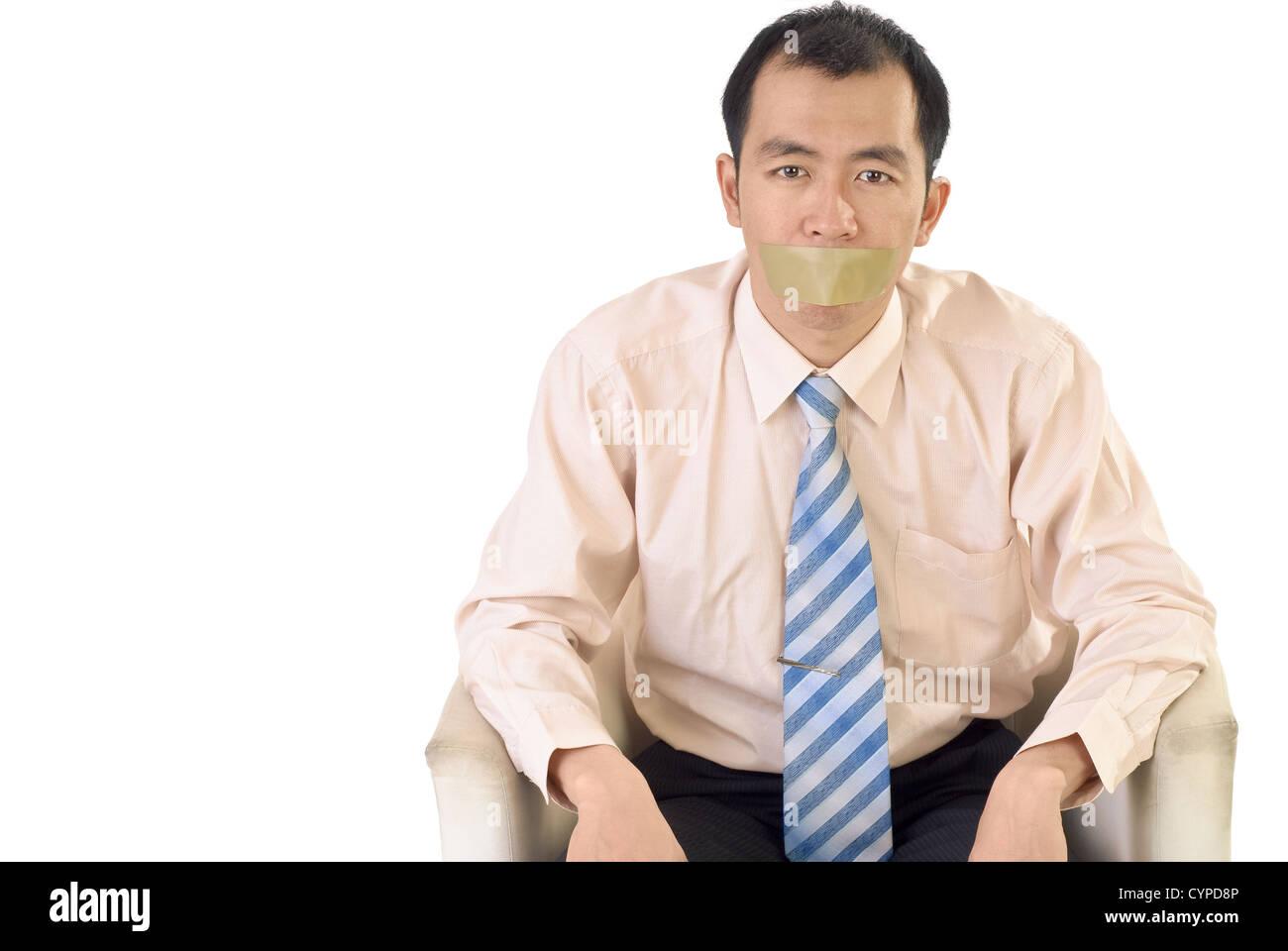 Imprenditore silenzioso con nastro adesivo sulla bocca a sedersi su sfondo bianco. Immagini Stock