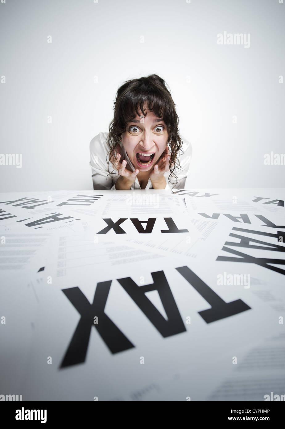 Stupito donna guardando un mazzetto di preoccupanti forme di imposta sulla sua scrivania Immagini Stock