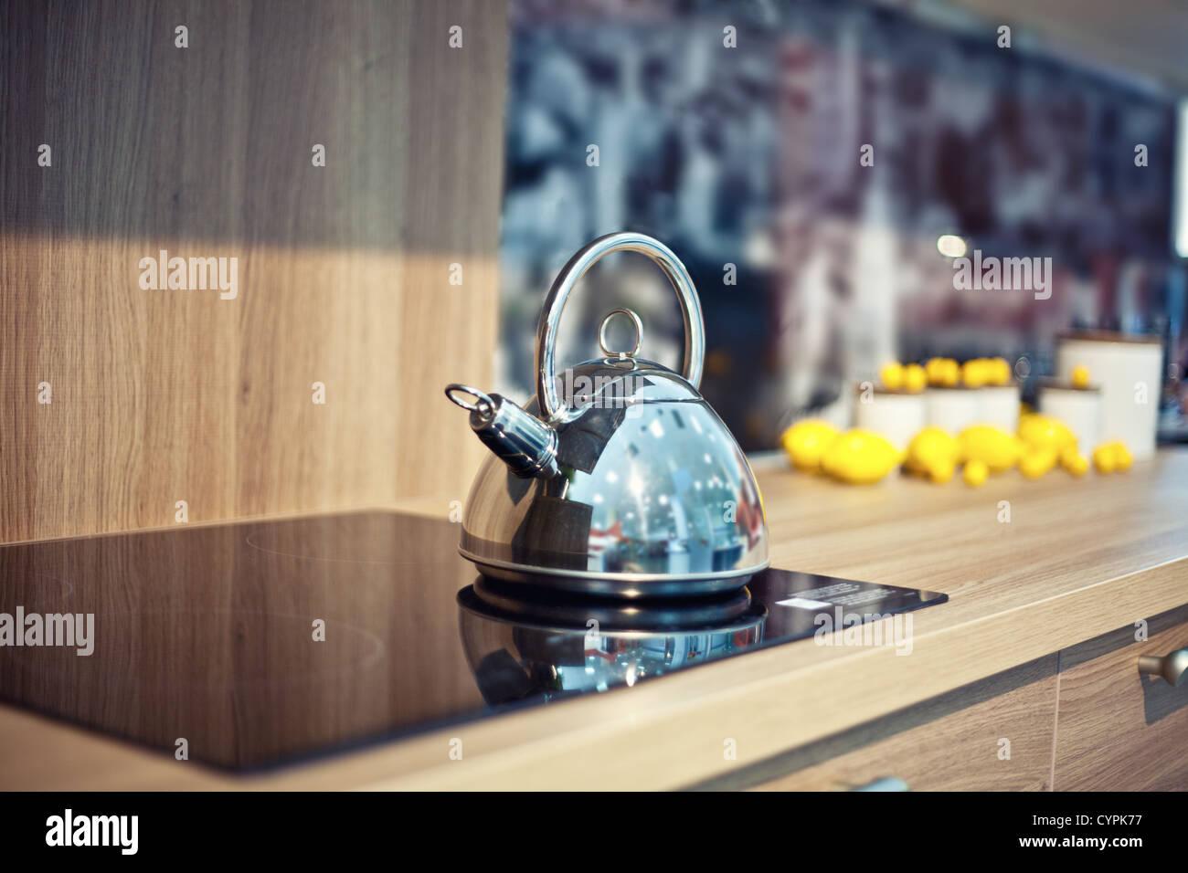 Shiny bollitore per il tè sul tavolo di cucina (bella diepth di effetto di campo) Immagini Stock